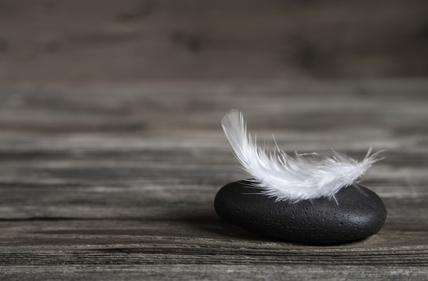Holz Hintergrund mit Stein und Feder als Trauerkarte